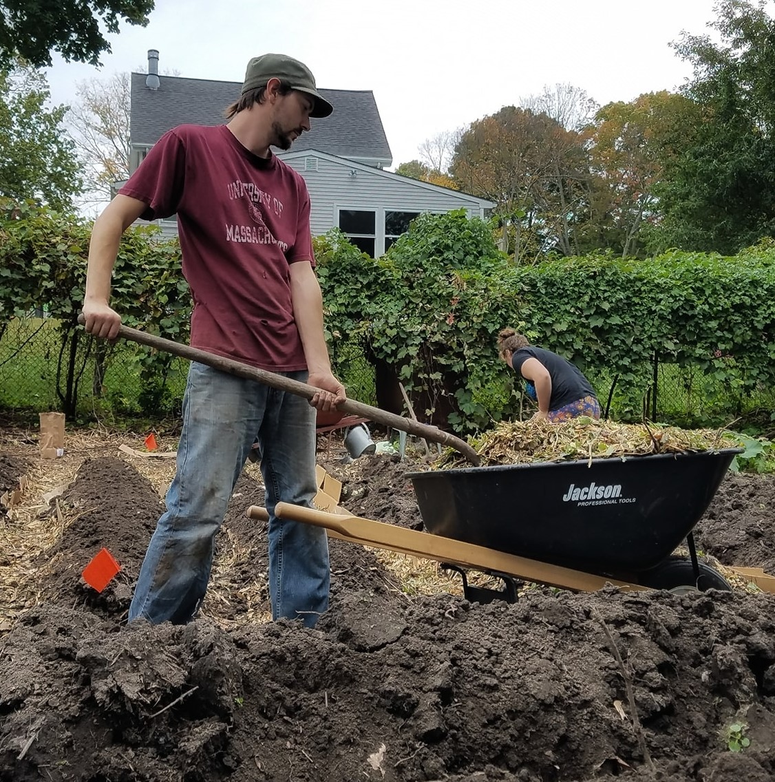 Jay in the field distributing wood chips from a wheelbarrow