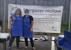 Meghan and her sister Hannah are at a farmers market, in front of the sign. They are wearing masks.