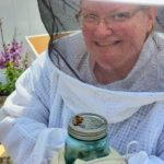 Meghan in a beekeeping outfit hold a jar with a few honeybees on top